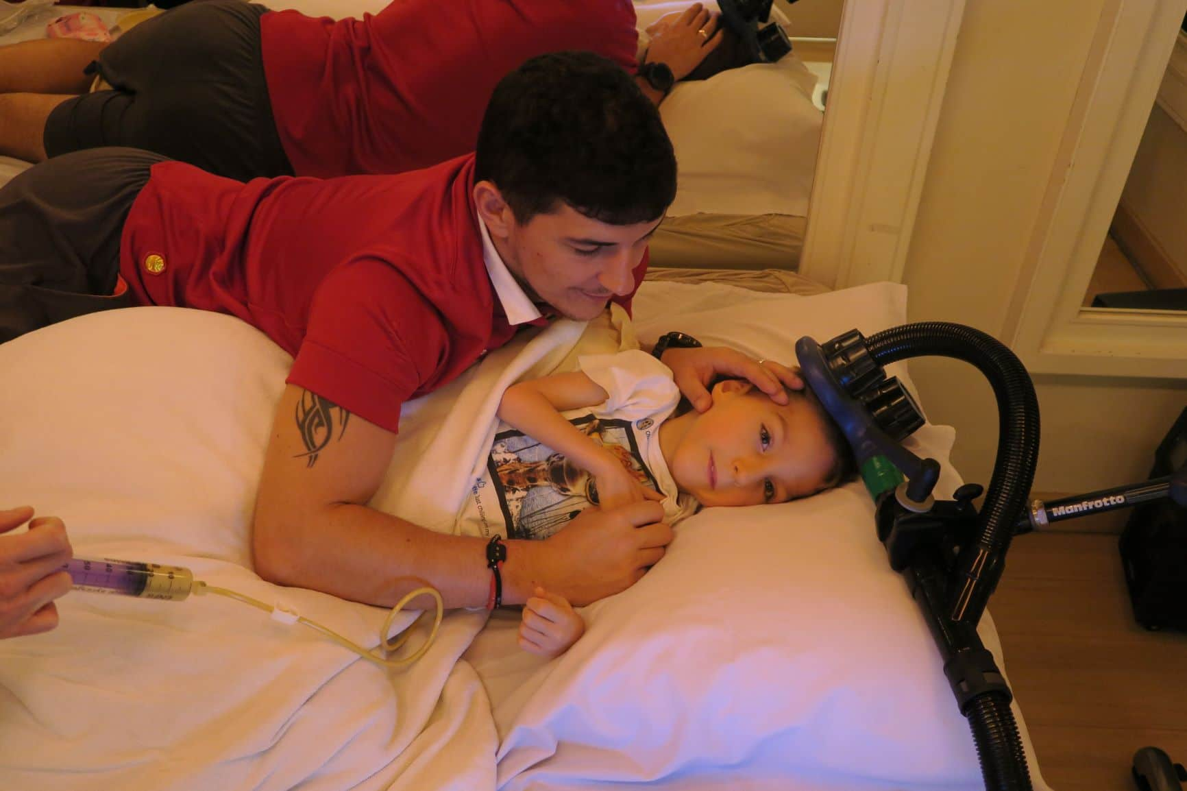 Image of Enzo with father as he receives transcranial magnetic therapy